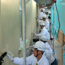 等間隔で慎重に塗装する施工チーム(写真・安田塗装)
