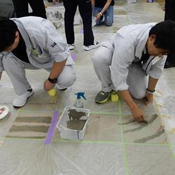 床面に色の違う塗料を乗せ、ダンボールの端材で櫛引き
