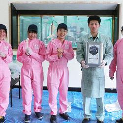 KP女子はピンクのつなぎで揃える。中央:中原むつ美さん