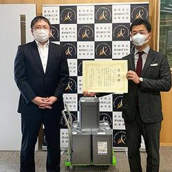 洗浄用アルコールを寄贈する名倉会長(右)